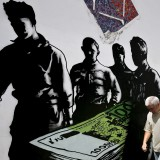 "A man makes his way past graffiti ""Death of euros"" made by French street artist Goin in Athens"