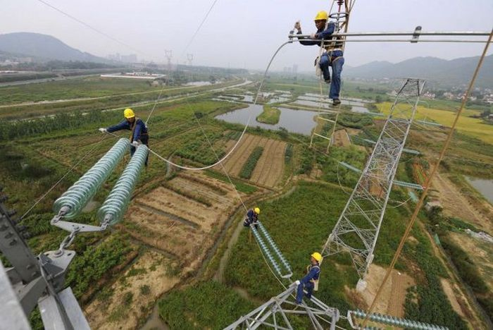Workers install cables on a electricity pylon above crop fields in Xihu township of Tongling